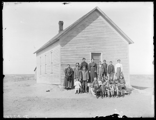 Group of students and teachers in front of the school at Riverdale, Buffalo County, Nebraska.