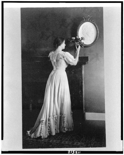 [Helen Keller, full-length portrait, facing right, standing at fireplace with flowers on the mantle]