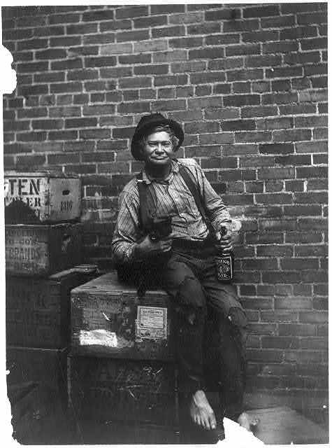"[""John Bour""[?] - barefooted, shabbily dressed man, sitting on crates, in front of brick wall, with arm around a cat, holding a bottle of Raleigh Rye whiskey]"