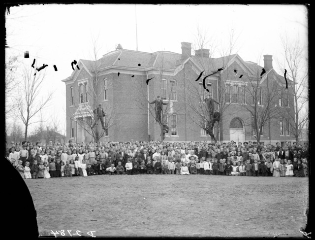 Large group of students and teachers in front of school building at Ord High School or St. Paul High School