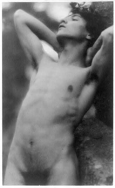 [Nude youth with laurel wreath against rock with hands behind neck, cropped at thighs]