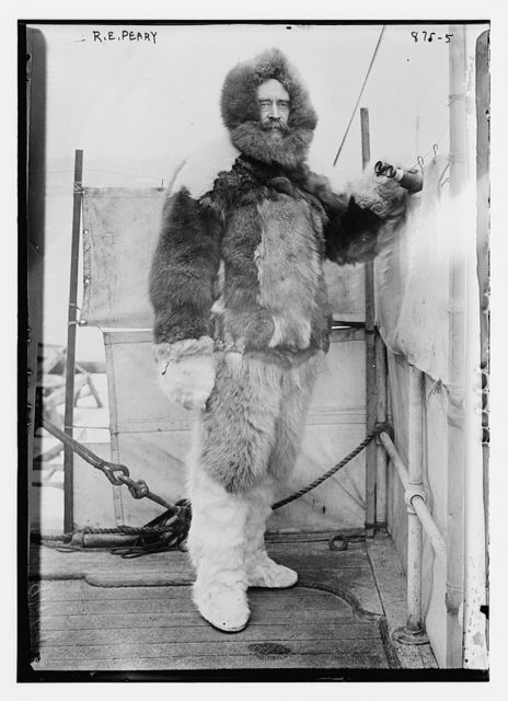 """R.E. Peary, on deck of """"Roosevelt"""" in fur parka, with binoculars"""