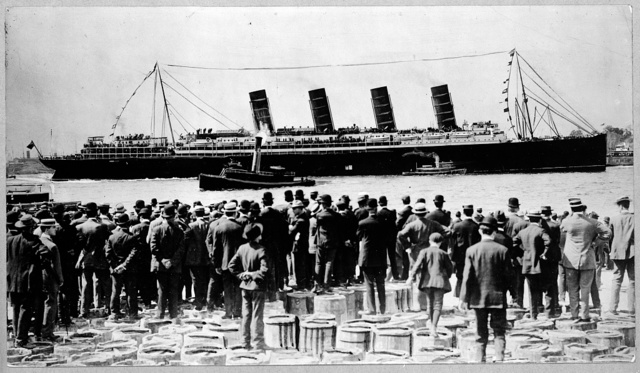 [RMS Lusitania, New York City, September 1907, stern-side view, during maiden voyage, with a large crowd of men, in foreground, standing on top of barrels]