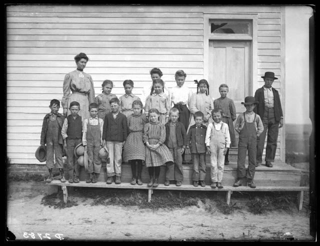 School children with their teacher, Miss Swenson, in front of a Buffalo County, Nebraska,  school house.