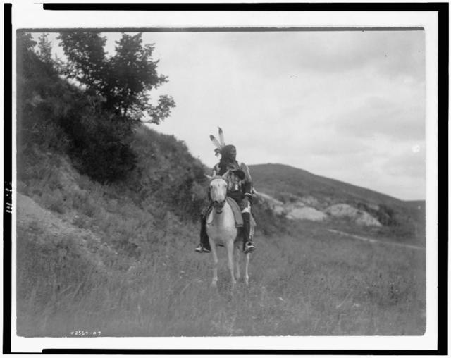 [Sioux Indian on horseback, wearing two feathers, beaded buckskin shirt, and leggings, with hills in background]