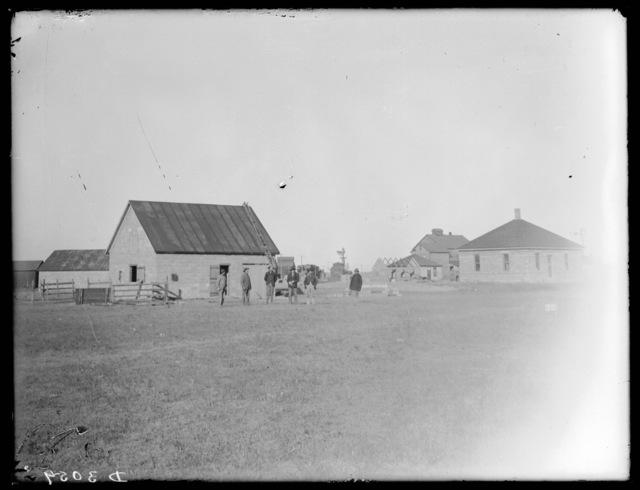 Six men standing near concrete block house and barn at Pleasanton, Nebraska.