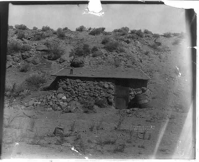 [Small rock and mortar hut built against hillside. Western U.S.]