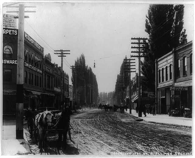 [Street scene in Lewiston, Idaho, including stores and horse-drawn wagons]