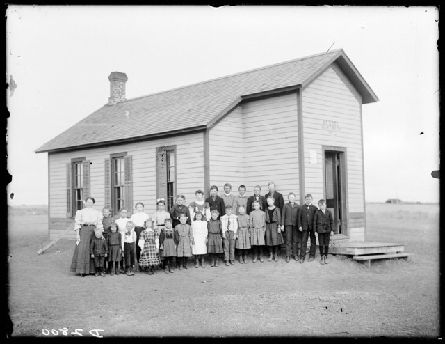Students and their teacher in front of   District #44 school, three miles north of Kearney, Nebraska.