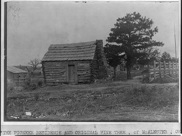 [The Pioneer residence and original pine tree of McAlester, Okla., old log cabin in foreground]