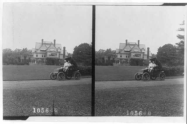 Thomas A. Edison and son(?) in automobile and large housein background
