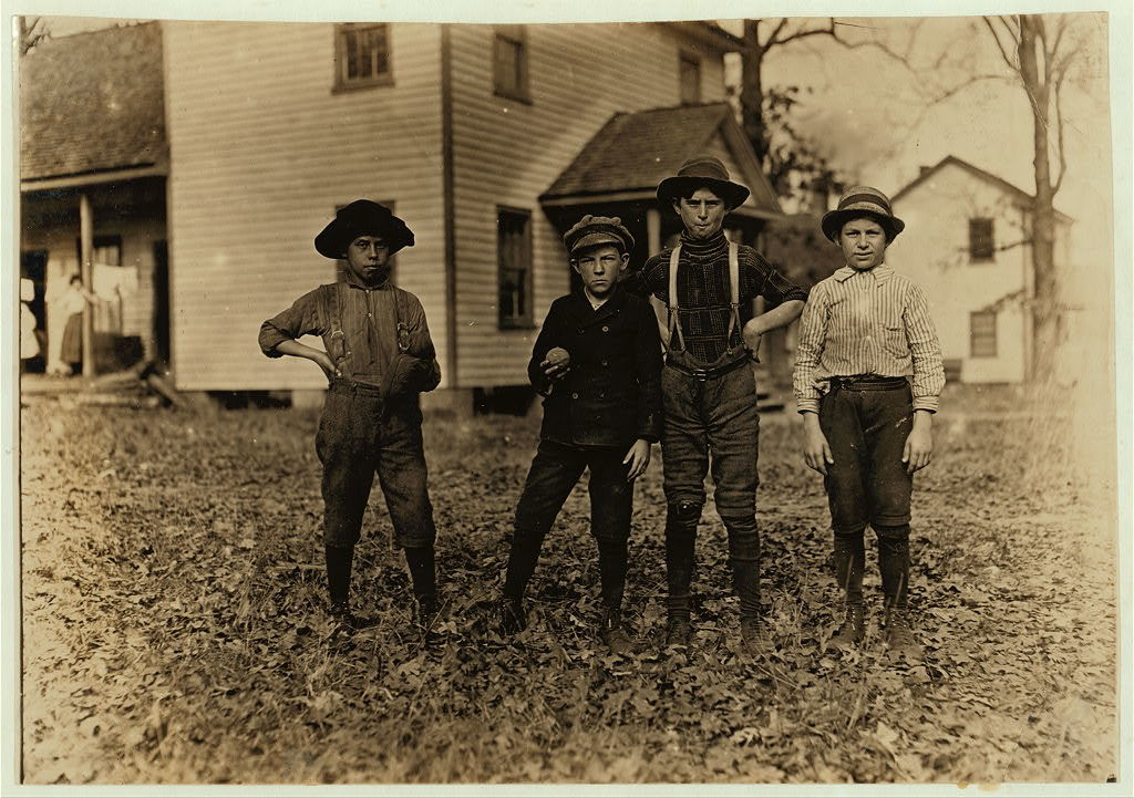 """A Saturday ball game. Springstein Mills, Chester, S.C. Boy with glove, Malcom Rogers. (See photo 329). Next to him - Ben Deaton--12 years old. 52 inches high. Weaver. Runs 6 looms at $1.00 a day. 2 years in mill. I asked him if it wasn't hard work. """"Hardest part if it is I have to stretch so much to reach up."""" (Tallest boy) John Lewis--12 years old. 1 yr. in mill. Weaves--4 looms. Got 40 cents to start. 60 cents now a day. Brother and father in mills. Nov. 28/08 Witness Sara R. Hine.  Location: Chester, South Carolina / Photo by Lewis W. Hine."""