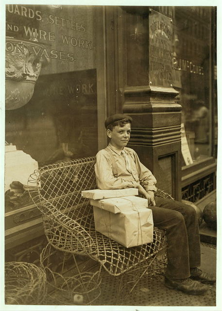 An Enforced Rest. Harry Swope, aged 15, 426 Elm St., Newport, Ky., Carrying heavy bundles of paper for a News & Sta'y Co.  Location: Newport, Kentucky.