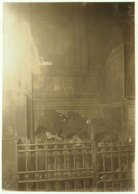 Asleep while waiting for morning papers. 11 P.M. February 11th, 1908. A grating at side of World Building, through which came a stream of warm air from ventilators. Various boys and men may be found here at different times of night and morning, staying until the policemen moves them on. (See No. 22[A] for two of these boys).  Location: New York, New York (State)