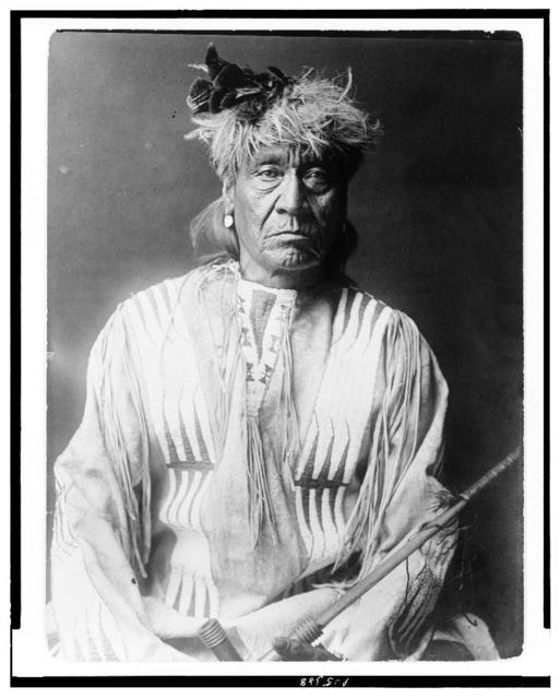 [Atsina Indian, Red Whip, half-length portrait, seated, facing front, wearing feather, beaded buckskin shirt, holding pipe in left hand]