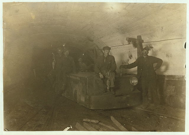 Bank boss, (with lamp between knees) Motorman, Brake-boy and Driver. Gary Mine, Gary, W. Va. Boss said he would use more boys if he could get them but they went to school. Note live wire on level with heads.  Location: Gary, West Virginia.