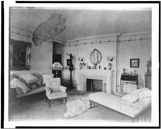 [Bedroom with fireplace, padded chaise longue, sofa, male nude statuette, and polar bear rug, in home of Edmund Cogswell Converse, Greenwich, Connecticut]