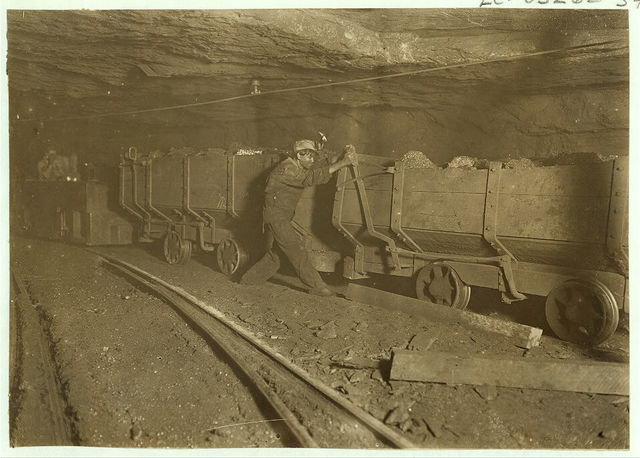 Boy braking on motor train 10 hrs. a day. Where mining, loading, etc. is done by machinery. Live wire above is sometimes not higher than a man's head.  Location: Gary, West Virginia.