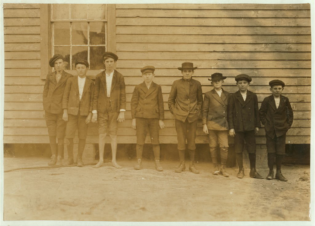 """Boys working in Scotland Mill, Laurinburg, N.C. Smallest boy--Junior Bounds--Beginning. Next, Rollin Hudson - 3 years in mill. Next, Lloyd Willoughby - 3 years in mill. Next, Preston Torrent - 8 years in mill. 6 years night work - 14 years old now. """"Haven't been in school more'n 3 days in my whole life."""" Father blind. 2 older sisters and 1 younger brother work in mill now. Has doffed all 8 years. Gets about 60 cents a day. Asked him if he didn't get tired, """"No, when you get used to it you don't get tired. Some of the boys goes to sleep when they begin."""" Showed a remarkable degree of refinement and consideration for others. Work has not blunted this. Sunday, Dec. 6/08. Witness, Sara R. Hine.  Location: Laurinburg, North Carolina / Photo by Lewis W. Hine."""