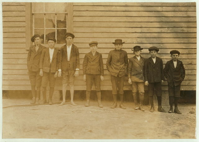 "Boys working in Scotland Mill, Laurinburg, N.C. Smallest boy--Junior Bounds--Beginning. Next, Rollin Hudson - 3 years in mill. Next, Lloyd Willoughby - 3 years in mill. Next, Preston Torrent - 8 years in mill. 6 years night work - 14 years old now. ""Haven't been in school more'n 3 days in my whole life."" Father blind. 2 older sisters and 1 younger brother work in mill now. Has doffed all 8 years. Gets about 60 cents a day. Asked him if he didn't get tired, ""No, when you get used to it you don't get tired. Some of the boys goes to sleep when they begin."" Showed a remarkable degree of refinement and consideration for others. Work has not blunted this. Sunday, Dec. 6/08. Witness, Sara R. Hine.  Location: Laurinburg, North Carolina / Photo by Lewis W. Hine."