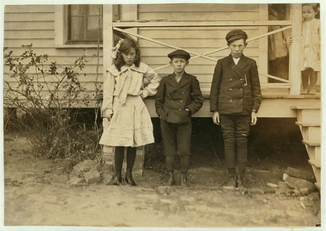Children of night superintendent, in Dickson Mill, Laurinburg, N.C. (1) Bessie Moore - runs 4 sides. Has worked two years nights. (2) Frank (smallest). Doffs. Has worked 2 yrs. nights. (3) George (largest). Looked 12 years old. Doffs--3 years of night work, was proud of the fact that he could write his name. Mother said they rather work nights because they had to put in fewer hours then. Sunday, Dec. 6, 1908. Witness, Sara R. Hine.  Location: Laurinburg, North Carolina / Photo by Lewis W. Hine.