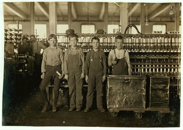 """Daniel Mfg. Co., Lincolnton, N.C. Four doffers. Boy on left end (knee pants) said he had worked in mills for 7 years and some nights. At nights they work 12 hours, without any hour off for lunch. Eat when they can. Some of the[m] """"eat a-workin'.""""  Location: Lincolnton, North Carolina."""