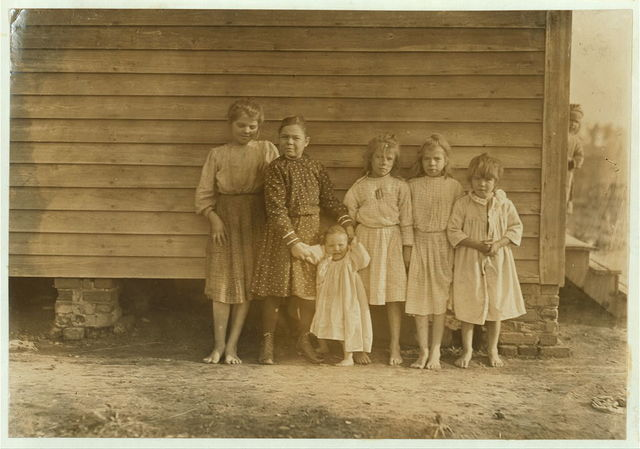 "Dillon Mill (tallest) Lizzie McKenzie, Has helped 1/2 year. Mamie Baxley (holding baby). Been in mill 3 years. Runs 4 sides = 40 cents a day. Maud & Daisy ""help.""  Location: Dillon, South Carolina."
