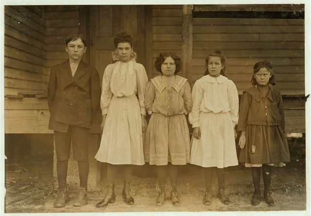 Dillon Mills, Dillon S.C. (Boy) Ransom English--doffs, been in mill 6 years. (Next) Florence Burr--runs 5 sides. In mill 4 years. (Next) Bessie English - 3 sides, 3 years in mill. (Next) Alphie Burr - 2 sides, 1 year in mill. (Next) Lela English, 1 year in mill. 48 inches high. Saturday, Dec. 5, 1908.  Location: Dillon, South Carolina / Photo by Lewis W. Hine.
