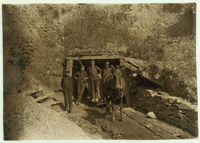 "Drift Mouth, San Lick Mine, near Grafton, W. Va. Bank Boss in centre: driver on his right: trapper boy outside. Alfred, about 14. He trapped several years during vacation: said he is going to school this year: asked if it were because school is more fun he said. ""This yere hain't no fun!"".  Location: Grafton, West Virginia."