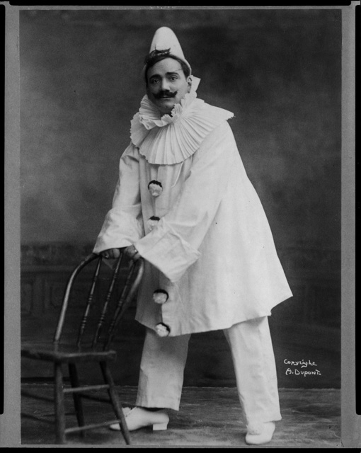 "[Enrico Caruso, 1873-1921, dressed as clown, holding back of chair, in ""Pagliacci""]"