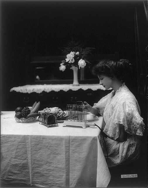 Gene and her friend using General Electric Heating and Cooking Devices: young woman seated at table, removing toast from toaster
