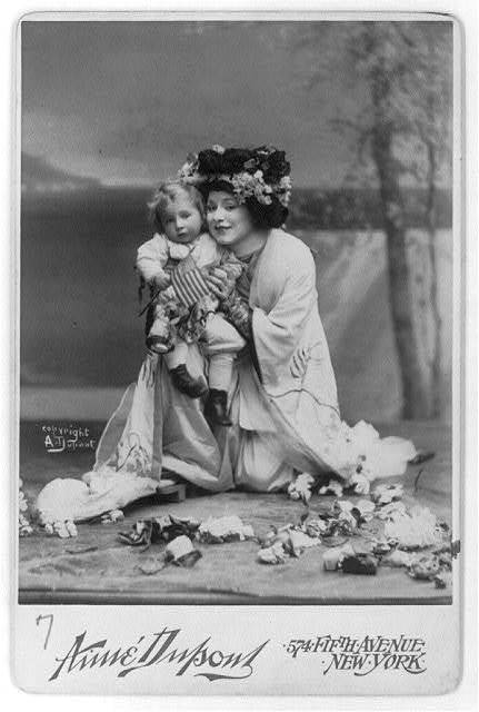 "[Geraldine Farrar, 1882-1967, full length, kneeling, facing left; in the role of ""Madame Butterfly"", wearing Oriental costume and holding a small child]"
