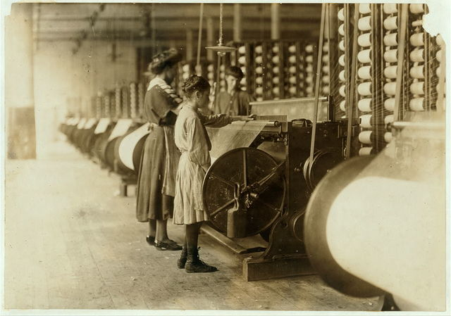 "Girls running warping machines in Loray mill, Gastonia, N.C. Many boys and girls much younger. Boss carefully avoided them, and when I tried to get a photo which would include a mite of a boy working at a machine, he was quickly swept out of range. ""He isn't working here, just came in to help a little.""  Location: Gastonia, North Carolina."