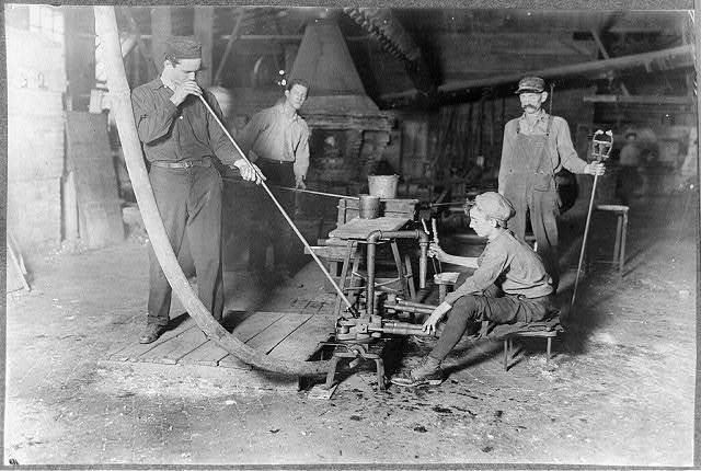 Glass Blower and Mold Boy. Boy has 4 1/2 hours of this at a stretch, then an hour's rest and 4 1/2 more: cramped position. Day shift one week: night shift next. (see label on photo 162.) Grafton, W. Va.  Location: Grafton, West Virginia.