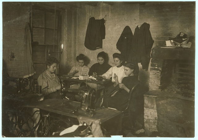 Group of women in sweatshop of Mr. Sentrei, 87 Ridge Street, second inner court. Small girl is Mamie Gerhino, 202 Elizabeth Street. She might have been 14 years old. Photo 5 P.M., February 21, 1908. Witness Mrs. Lillian Hosford.  Location: New York, New York (State) / by Lewis W. Hine.