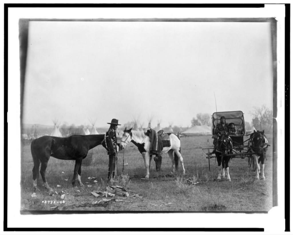 [High Medicine Rock, Crow Indian with two horses at left, Her Horse Kills with child in buggy at right, tepees and circus type tent in background, Montana]