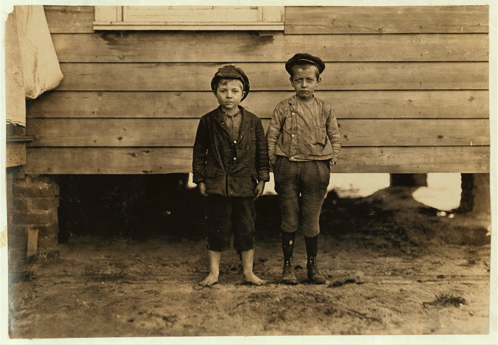 """In neighborhood of Maple Mill, Dillon, S.C. Lawrence Faircloth (taller boy) """"Don't know how old I am."""" Been in mill 2 years. Runs 3 sides Albert Bartlett (barefoot) Looked 8 years old. In mill 2 years--Beginning to spin. Runs 2-1/2 sides = 25 cents a day. Bad conditions. Saturday, Dec. 5, 08.  Location: Dillon, South Carolina / Photo by Lewis W. Hine."""