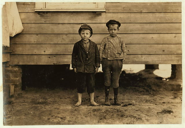 "In neighborhood of Maple Mill, Dillon, S.C. Lawrence Faircloth (taller boy) ""Don't know how old I am."" Been in mill 2 years. Runs 3 sides Albert Bartlett (barefoot) Looked 8 years old. In mill 2 years--Beginning to spin. Runs 2-1/2 sides = 25 cents a day. Bad conditions. Saturday, Dec. 5, 08.  Location: Dillon, South Carolina / Photo by Lewis W. Hine."