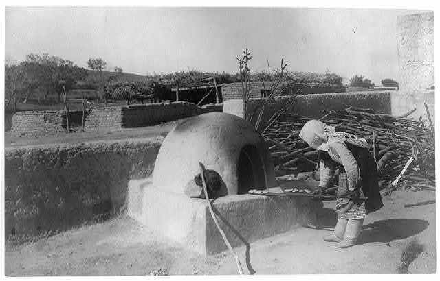 "[Indian woman baking in outdoor oven. ""Par-dah-weh""; Southwestern U.S.]"