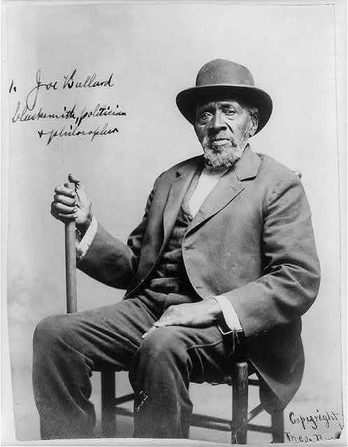 "[Joe Ballard, three-quarters length, seated, facing slightly left, ""blacksmith, politican, and philosopher""]"
