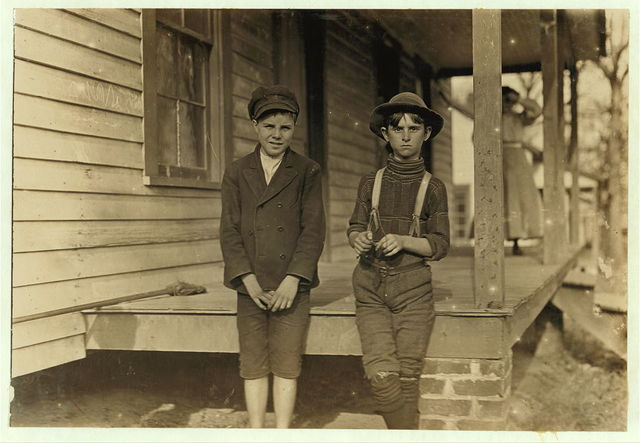 """John Lewis (boy with hat) 12 years old. 1 year in mill. Weaver--4 looms. 40 cts. to start, 60 cents a day now. Brother and mother in mill. Morris Small (boy with cap) """"Reckon I been in mill 2 yrs. Don't remember."""" Witness S.R. Hine.  Location: Chester, South Carolina."""