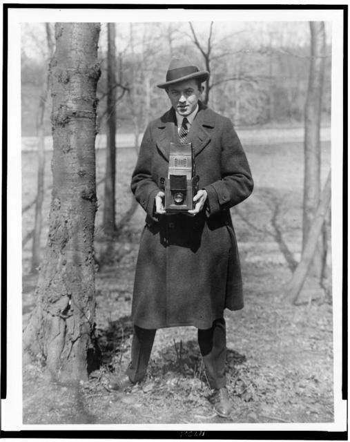 [John Steel, full-length portrait, holding camera in a wooded area]