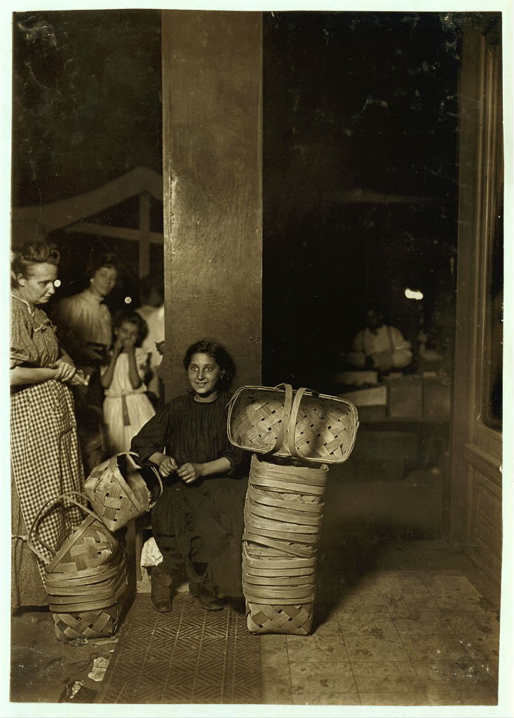 Lena Lochiavo, 11 years old, Basket Seller, Sixth St. Market, Cincinnati O. Saloon entrance. 11 P.M. Had been there since 10 A.M. and not yet sold out.  Location: Cincinnati, Ohio.