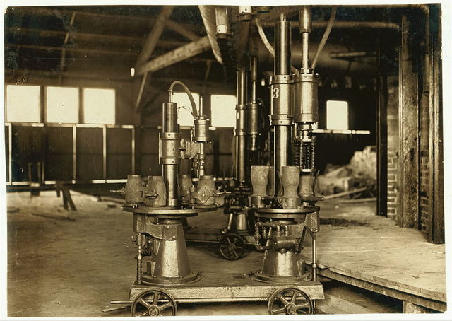 """Machine that blows 4 milk bottles at a time. No """"lung blowers"""" employed. Travis Glass Co., Clarksburg W. Va. Manager says machines are fast coming into play in bottle industry, plans eventually to have machines in place of """"carrying in boys.""""  Location: Clarksburg, West Virginia."""