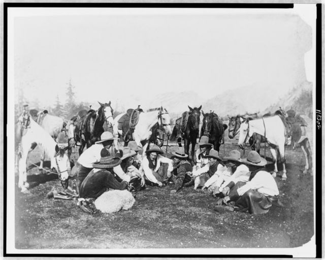 [Members of Pawnee Bill's Wild West Show seated in semicircle, with horses behind them]