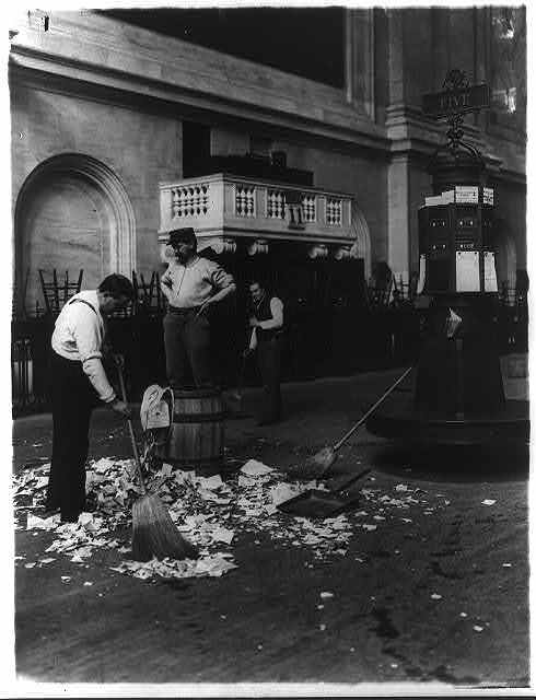 Men sweeping up the floor of the stock exchange