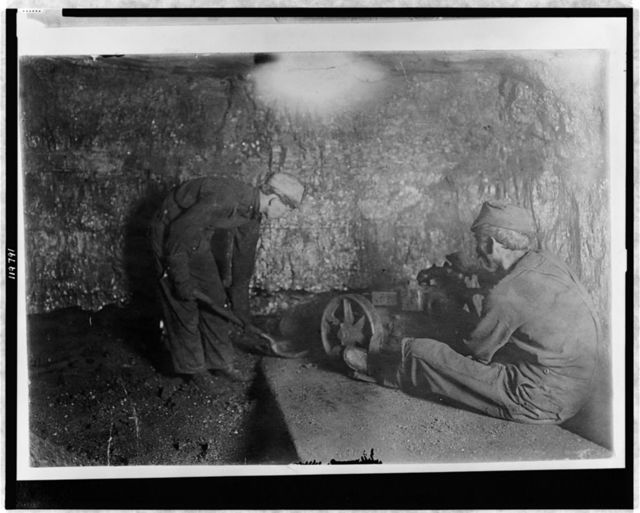 National Child Labor Committee, No. 69. Man with punching machine to drill into coal. Boy shovels out 10 hrs. daily, Laura Mine, Red Star, W. Va.  Location: Red Star, West Virginia.