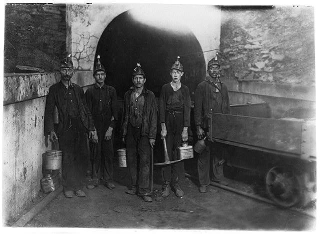 """National Child Labor Committee. No. 92. Main entrance Gary W. Va. Mine. Miners going into mine 7 A.M. Boy beginning career as """"picker."""" Will be in mine over 10 hours consecutively. 7 A.M. to 5:30 P.M.  Location: Gary, West Virginia."""