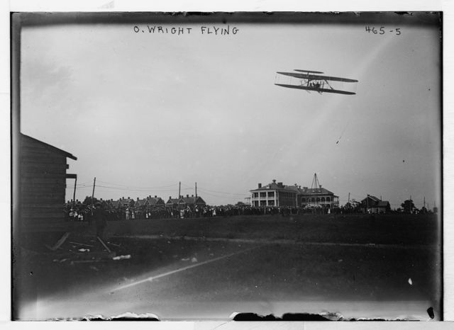 O. Wright flying [in his airplane, crowd on field]