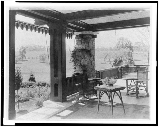 [Porch with wicker furniture, and view over lawn to home of Edmund Cogswell Converse, Greenwich, Connecticut]